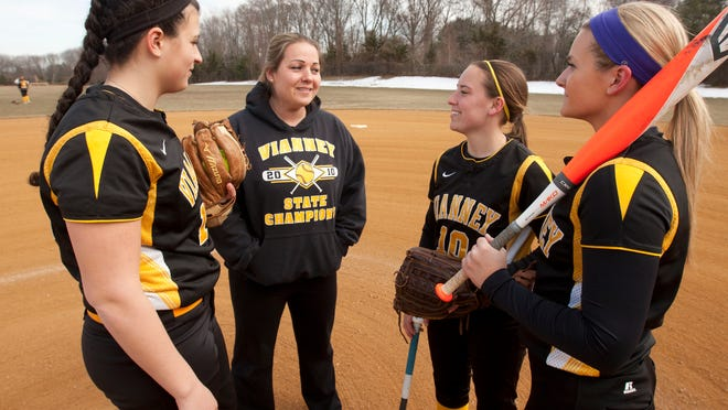 St. John Vianney softball coach Kim Lombardi (second from left) talks with players Ashley Ventura (left), Erica Krumbine (10) and Helena Coppola (right).