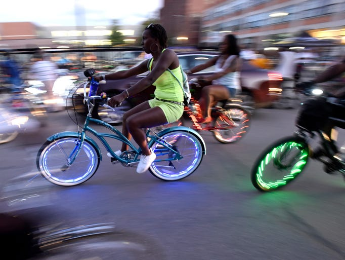 Riders return from the Slow Roll with their bikes lit