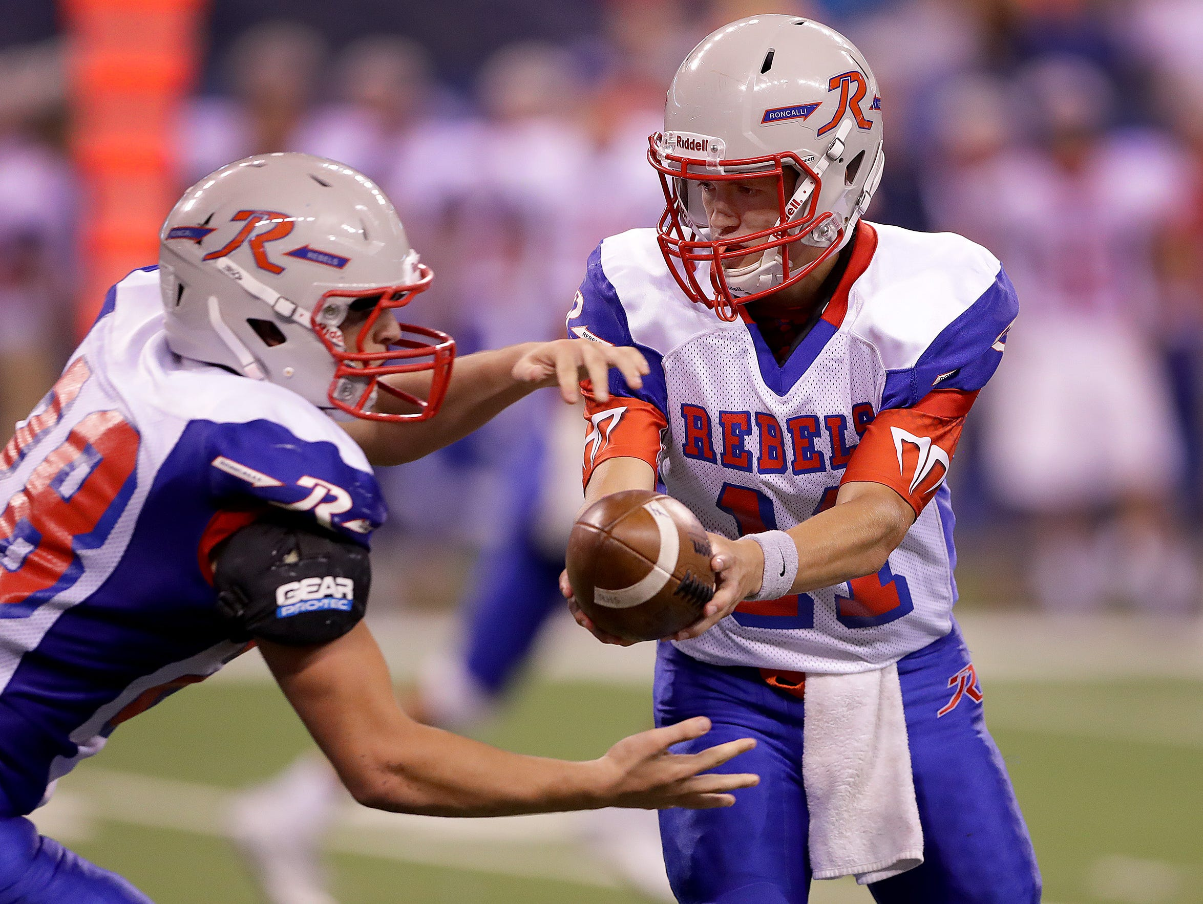 Roncallli's Derek O'Connor (11) hands the ball off to running back Kenny Gillum,left, in the second half. The Roncallli Rebels defeated the Franklin Central Flashes 22-14l Friday, August 26, 2015, evening at Lucas Oil Stadium.