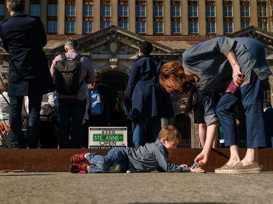 Hendrick Elmes of Detroit plays with his toy cars while waiting with his mother Philippa Kaye of Detroit for Matthew Moroun to speak in front of the Michigan Central Station about the sale of the station in Detroit to Ford Motor Company on Monday, June 11, 2018.