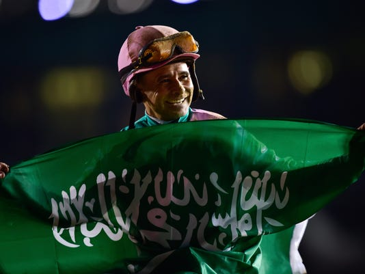 Jockey Mike Smith with horse Arrogate (not shown) celebrates after winning the U.S. $ 10,000,000 Dubai World Cup horse racing at the Meydan Racecourse in Dubai, United Arab Emirates, Saturday, March 25, 2017.  (AP Photo)