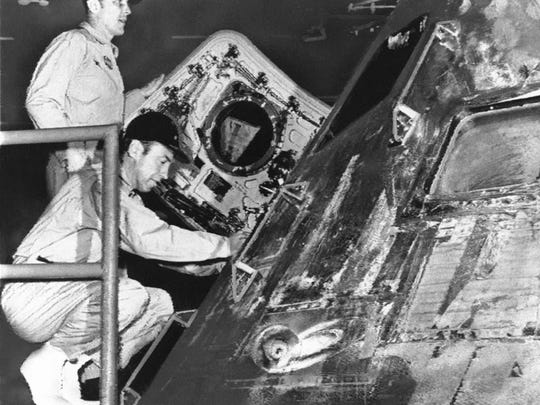 Safely aboard the prime recovery ship, USS Iwo Jima, astronauts James Lovell (squatting) and John Swigert inspect the Apollo 13 command module that carried them to a safe splashdown in the South Pacific April 17, 1970. The command module was carried to the hanger deck of the Iwo Jima.