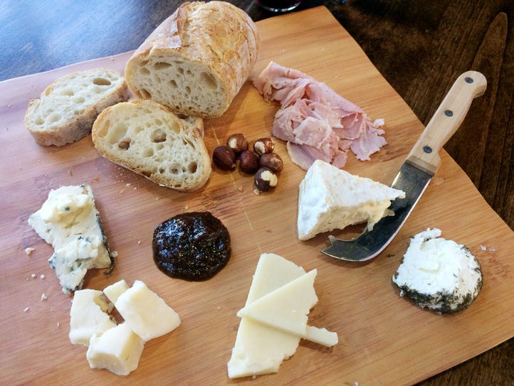 Cheese board with ham, fig preserves, toasted hazelnuts,