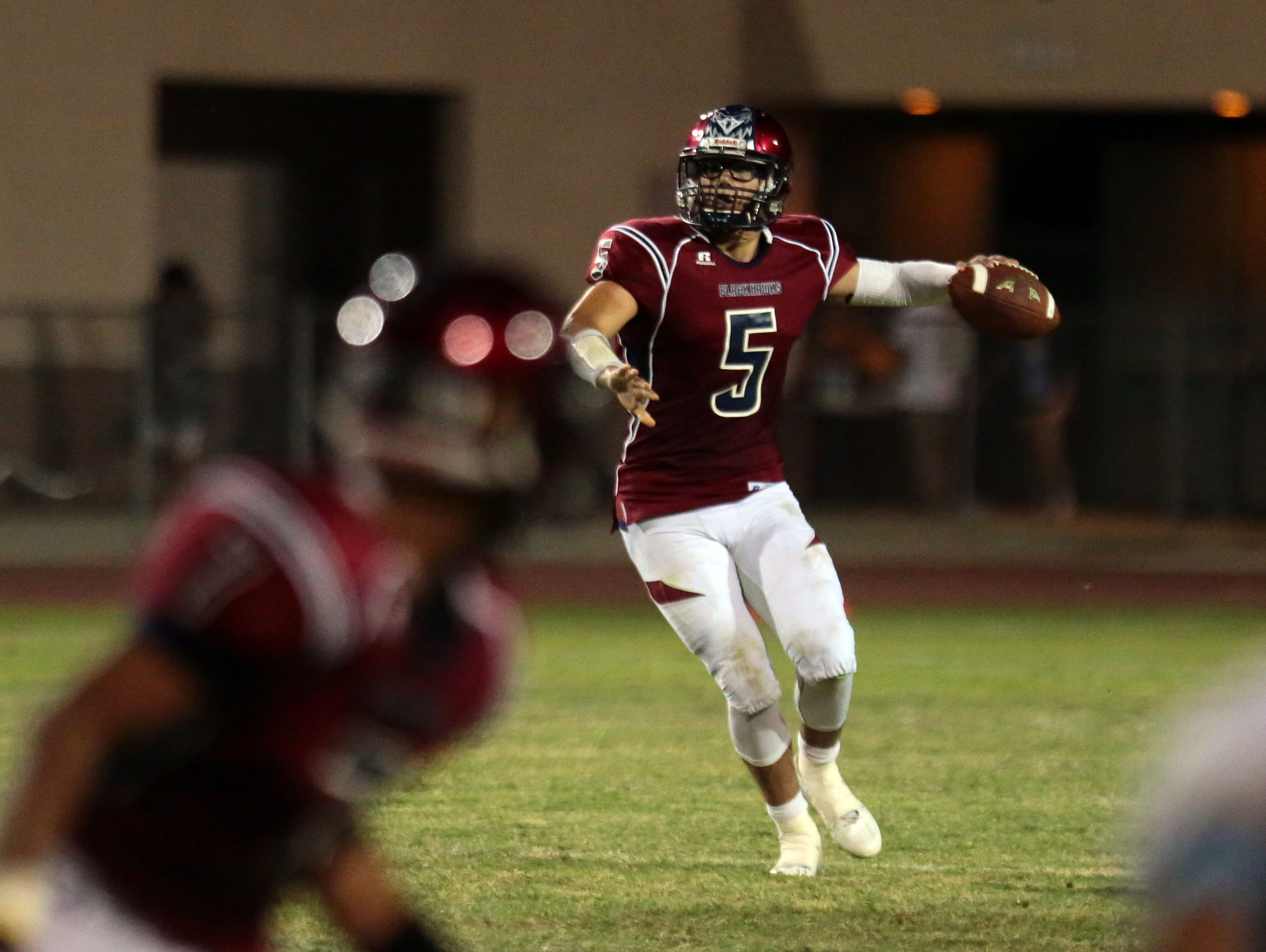 La Quinta quarterback Andrew Garcia hands the ball off to Justin Anderson during play against Rancho Mirage on Friday, September 9, 2016 in La Quinta.