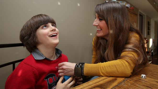 Katie O'Bryan, right, lets her son Trey Mauzy, 7, hear air expelling from a balloon as they play a game called Boom Boom Balloon at their eastern Jefferson County home.  Trey is totally blind and attends the Kentucky School for the Blind which is undergoing changes.  The game is designed to improve organizational, math and motor skills.Jan. 6, 2015