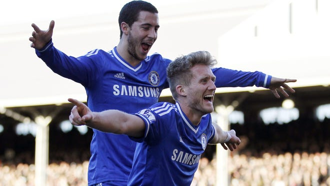 Chelsea striker Andre Schurrle, right, celebrates scoring his third goal to complete his hat trick with Chelsea midfielder Eden Hazard during the match between Fulham and Chelsea at Craven Cottage in London.