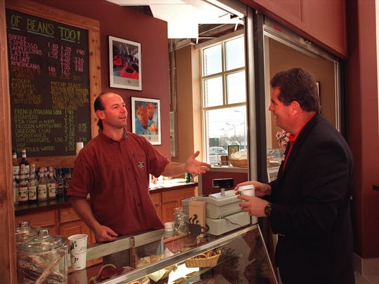 Dave Ferland, left, serves customer Ron Clevenger at the Hill of Beans Too cafe and coffee shop in the CATA Transportation Center in Lansing, April 6, 1998.