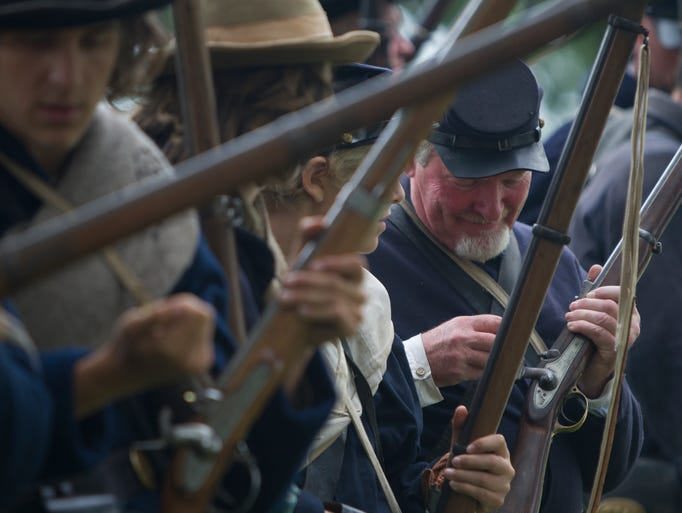 Tom Bowers (right) from Chili loads his gun before going to reenact a Civil War battle at the Tinker Homestead and Farm Museum in Henrietta on Sunday, August 3, 2014.