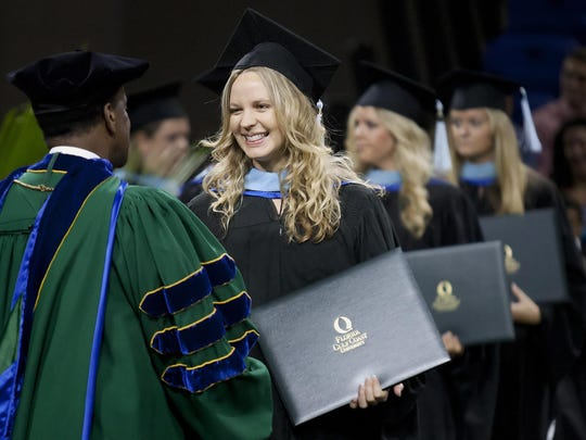One of the main goals for FGCU and President Wilson Bradshaw, seen here presenting a diploma at the 2014 graduation ceremony to Rachel Anderson, is to improve graduation rates.