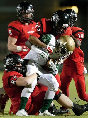 South Fort Myers High School defenders tackle Island Coast running back Van Edwards for a loss Friday at South Fort Myers.