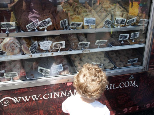 A child looks over a selection of pastries from Cinnamon Snail, a food truck that will offer its vegan and organic items at the Red Bank farmers market.