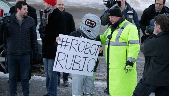A police officer tells an anti-Marco Rubio demonstrator