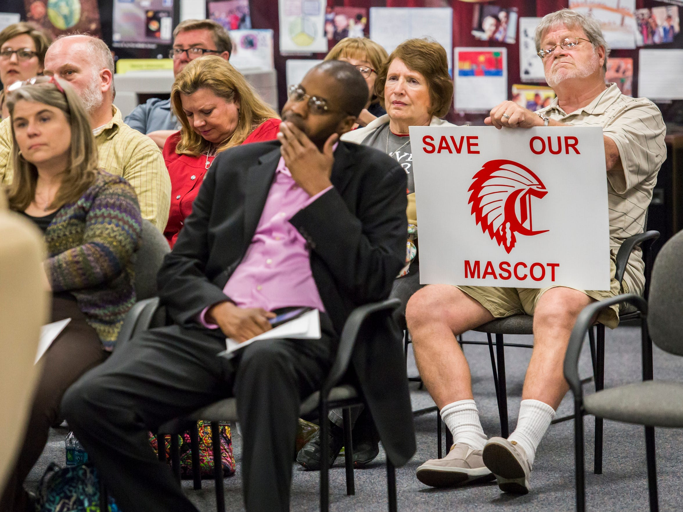 """Tim Laushey, a 1967 Conrad High School graduate and alumni band director, holds a sign reading """"Save Our Mascot,"""" at a meeting over the use of the Redskins logo in Elsmere on Monday. A committee is suggesting to change the logo."""