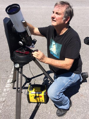 Pensacola State College astronomy professor Wayne Wooten looks at the sun using a solar telescope outside the planetarium on the school's main campus on Tuesday, Aug. 1, 2017.