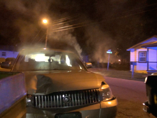 A car smokes after wrecking in a yard at the corner