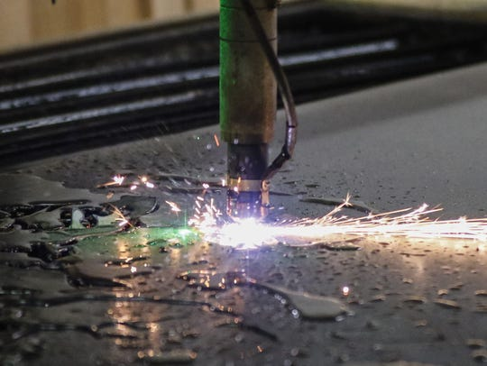 A close-up of the plasma cutter cutting a design in
