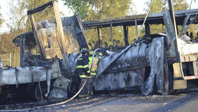 Firefighters hose down the wreckage of a bus and a semitruck that collided, Thursday, April 10, 2014, just north of Orland, Calif., that left at least nine dead. Authorities said it is not yet clear what caused the crash but that it involved a tour bus, a FedEx truck and a Nissan Altima.