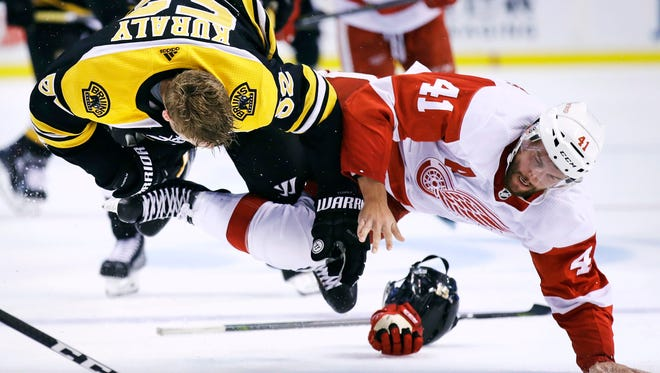 Red Wings center Luke Glendening (41) and Bruins center Sean Kuraly (52) drop each other to the ice during a fight in the second period of a preseason game on Tuesday, Sept. 19, 2017, in Boston.