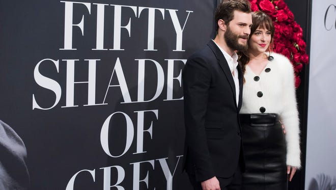 """Jamie Dornan and Dakota Johnson attend a special fan screening of """"Fifty Shades of Grey"""" hosted by The Today Show at the Ziegfeld Theatre on Friday, Feb. 6, 2015, in New York. (Photo by Charles Sykes/Invision/AP)"""