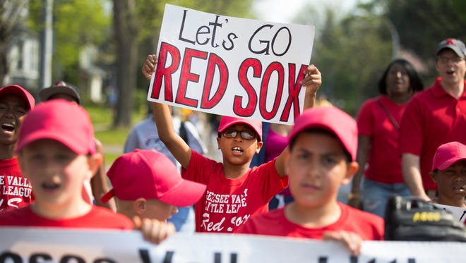 Anthony Grissett, 9, holds a sign in honor of his team as they walk in the Genesee Valley Little League opening day parade on Saturday, May 9, 2015.