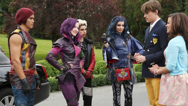 Good against evil? Disney villains' offspring Jay (Booboo Stewart, left), Mal (Dove Cameron), Carlos (Cameron Boyce) and Evie (Sofia Carson) meet royal spawn Ben (Mitchell Hope) and Audrey (Sarah Jeffery), in a scene from Disney Channel's 'Descendants.'