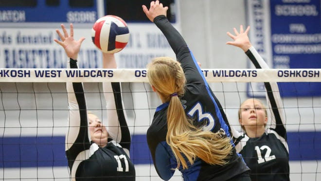 Ashley Shea (13) of Oshkosh West spikes the ball past Cece Dardis (17) fo Fond du Lac. The Oshkosh West Wildcats hosted the Fond du Lac Cardinals in volleyball Thursday evening, September 3, 2015.