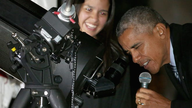 In and effort to promote science, technology, engineering and mathematics (STEM) education, President Obama gets a little help from Brooklyn, NY, student Agatha Sofia Alvarez-Bareiro while looking at the moon through a telescope during the second Astronomy Night on the South Lawn of the White House Monday. Obama hosted 300 scientists, engineers, astronauts, teachers and students for an evening of stargazing.