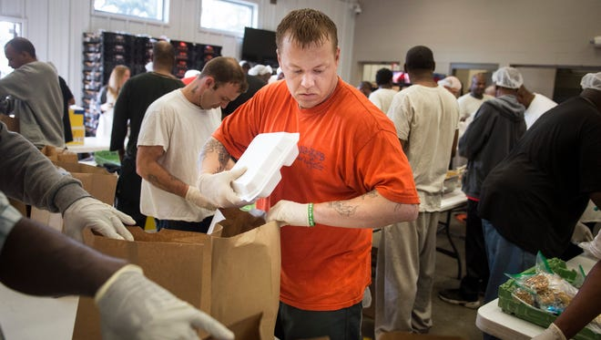 Troy Allen Bridges, 32, who has been in the transitional work program for three and a half months, bags lunches at the Ouachita SheriffÕs Office Transitional Work Program facility, Thursday, March 17, 2016, in Monroe, La. Inmates from the transitional work program helped package lunches to be distributed as part of flood relief efforts in Monroe.