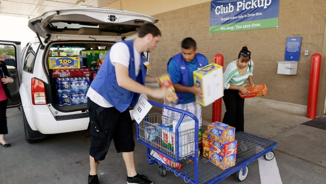 A Sam's Club customer, right, and store workers load previously ordered merchandise into a van at a pickup location at the Bentonville, Ark., store. On June 15, 2015.