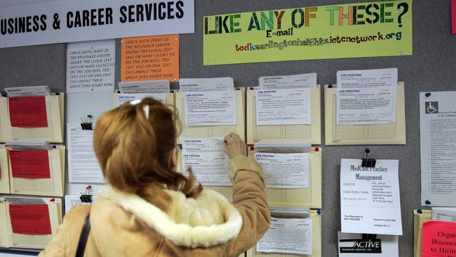 A woman looks at a job board at an Illinois Employment and Training Center.