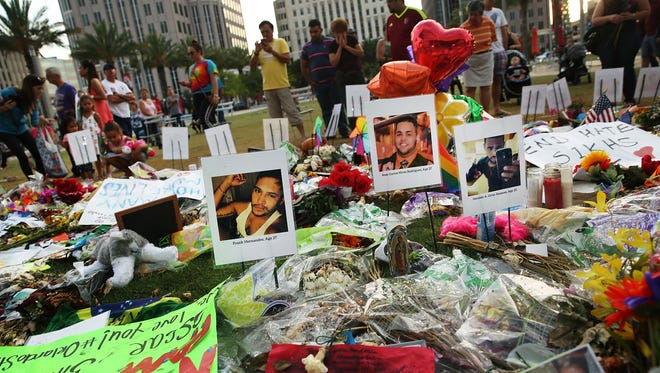 People visit a memorial on June 16, 2016, for those killed at the Pulse nightclub in Orlando. l