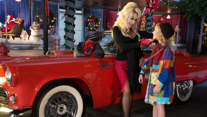 DOLLY PARTON'S CHRISTMAS OF MANY COLORS: CIRCLE OF LOVE --  Pictured: (l-r) Dolly Parton as The Painted Lady, Alyvia Alyn Lind as Dolly Parton -- (Photo by: Annette Brown/NBC)