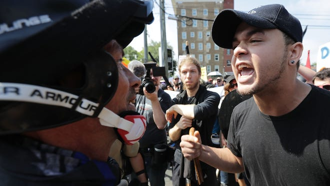 """White nationalists, neo-Nazis and members of the """"alt-right"""" exchange insults with counter-protesters as they enter Lee Park during the """"Unite the Right"""" rally Aug. 12, 2017 in Charlottesville, Va."""
