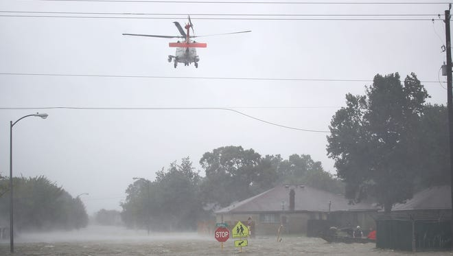 HOUSTON, TX - AUGUST 28:  A Coast Guard helicopter flies over a neighborhood after the area was inundated with flooding from Hurricane Harvey on August 28, 2017 in Houston, Texas. Harvey, which made landfall north of Corpus Christi late Friday evening, is expected to dump upwards to 40 inches of rain in Texas over the next couple of days.  (Photo by Joe Raedle/Getty Images) ORG XMIT: 775030825 ORIG FILE ID: 840305950