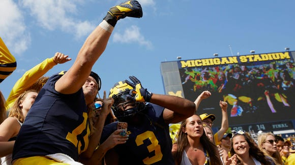 Michigan Wolverines defensive lineman Chase Winovich (15) and Michigan Wolverines defensive lineman Rashan Gary (3) take a selfie with the student section after defeating the Cincinnati Bearcats at Michigan Stadium on Sept. 9, 2017.