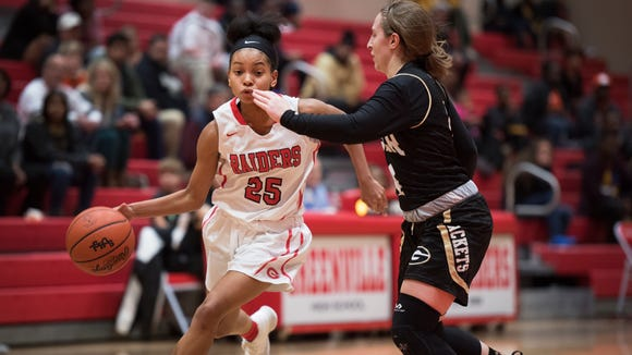 Greenville's Trinity Franklin (25) drives against Greer's Megan Jones during the Red Raiders' 59-41 win Friday night.