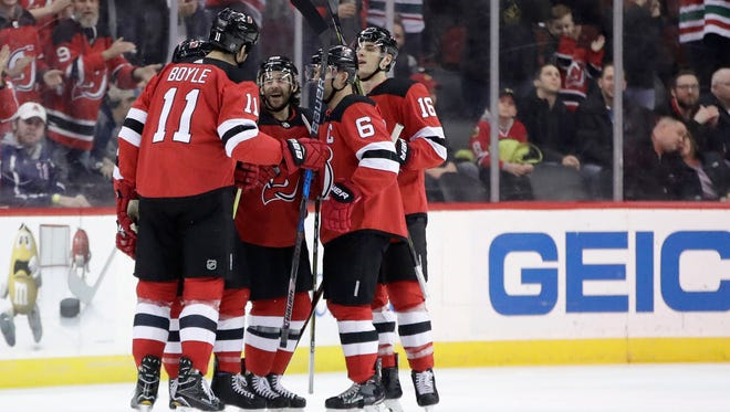 New Jersey Devils players celebrate a goal by center Brian Boyle (11) during the first period of an NHL hockey game against the Chicago Blackhawks, Saturday, Dec. 23, 2017, in Newark, N.J.