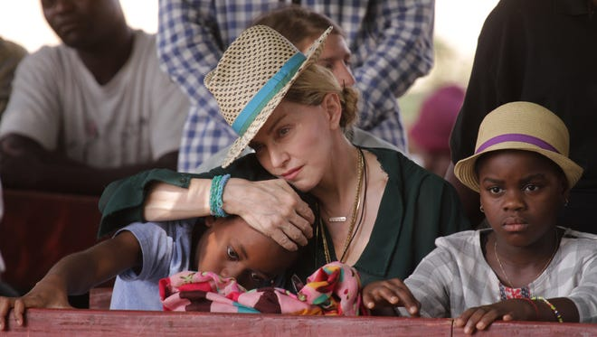 Madonna hugs her son, David, while her daughter, Mercy, looks on in Kasungu, about 90 miles north of the capital Lilongwe on Sunday, Nov. 30, 2014. Both children were born in Malawi before being adopted.