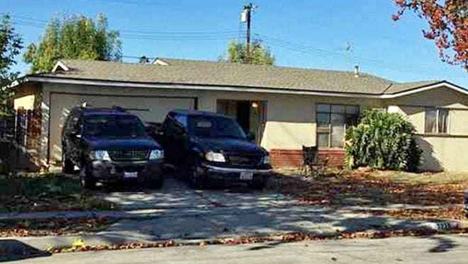 Vehicles are parked outside a home where Los Angeles County authorities say a man shot and killed his wife and two others on New Year's Eve before his son wrestled the gun away and fatally shot him.
