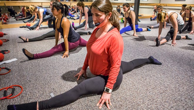 Maura Markley, owner of Pure Barre Greenville, demonstrates proper form as she leads a class on Wednesday, March 30, 2016.