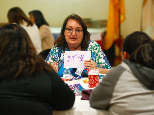 Beth Troxell of the Farmington Public Library participates in an exercise with her colleagues Wednesday during the Restoring and Celebrating Family Wellness program at the Office of Diné Youth in Shiprock.