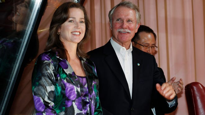 In this Sept. 13, 2011 file photo, Oregon Gov. John Kitzhaber, right, and his companion, Cylvia Hayes, react to a welcome from attendees at the awarding ceremony of the Enjoy Oregon Wine Fair in Tokyo