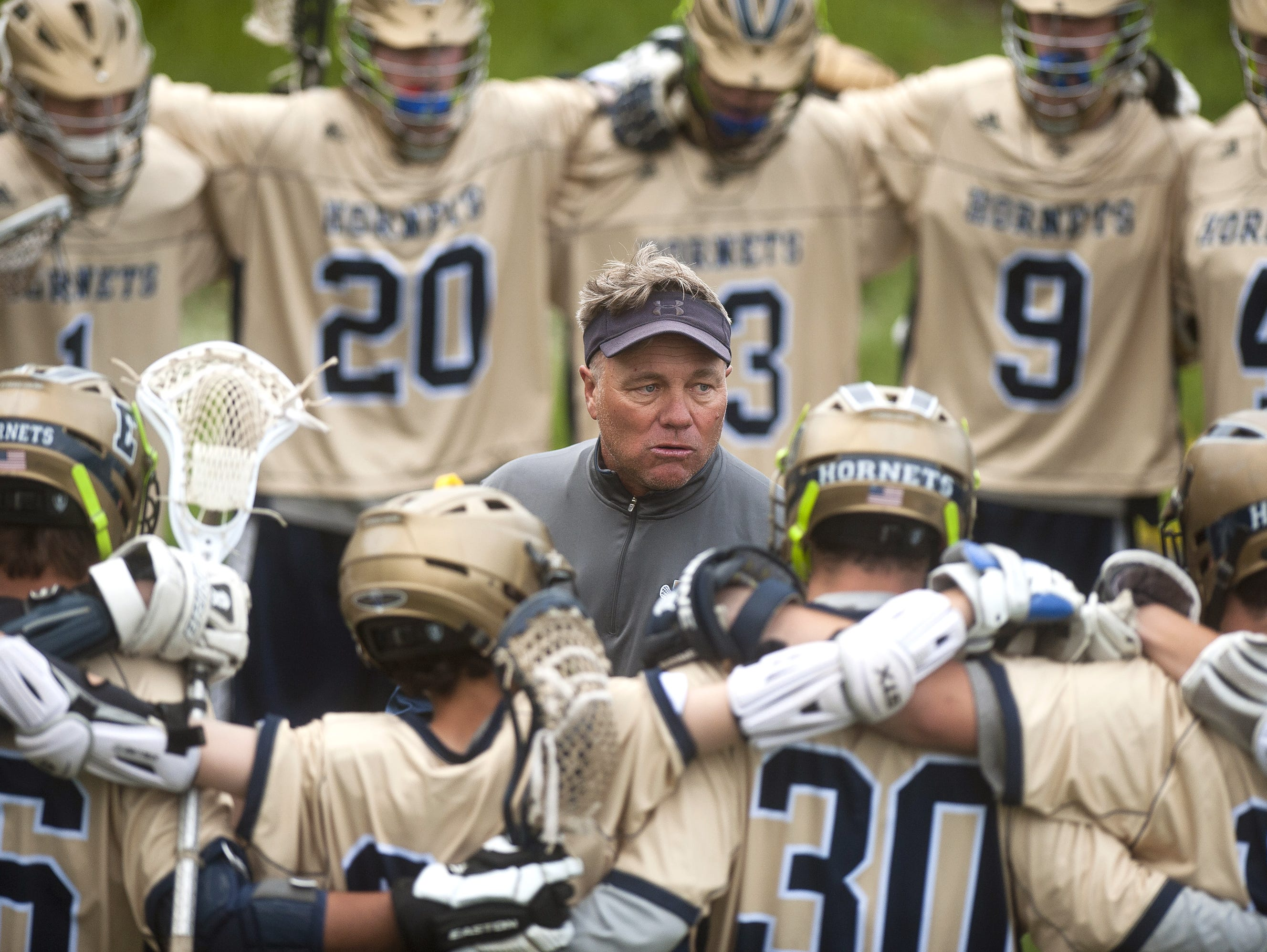 Essex boys lacrosse coach Dean Corkum, center, talks to his team during halftime of Tuesday's Division I semifinal at Middlebury College.