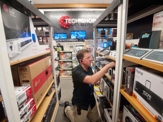 Erick Donley, housewares supervisor at Kohl's Oxmoor, straightens electronic  items.