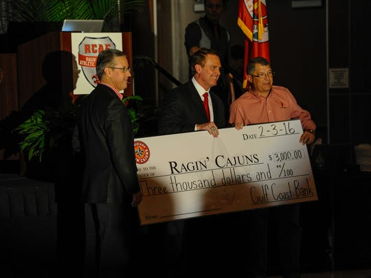 UL athletic Director Scott Farmer, left,  \and football coach Mark Hudspeth (with tie) pose at a check presentation.
