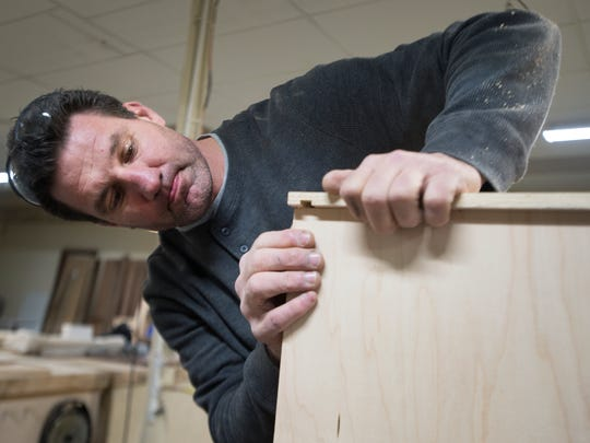 Brendan Carpenter, owner of Brendan Carpenter Custom Furniture and Refinishing, makes a cupboard for his new shop in Wellford on Friday, February 5, 2016.
