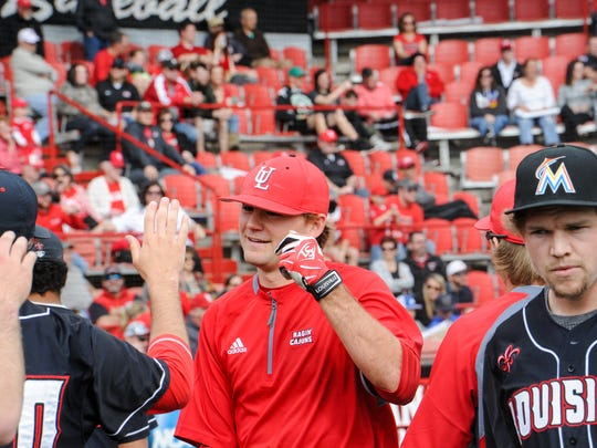 """UL's Stefan Trosclair (in red) takes part in the UL baseball team's Fan Day last Sunday at M.L. """"Tigue"""" Moore Field."""