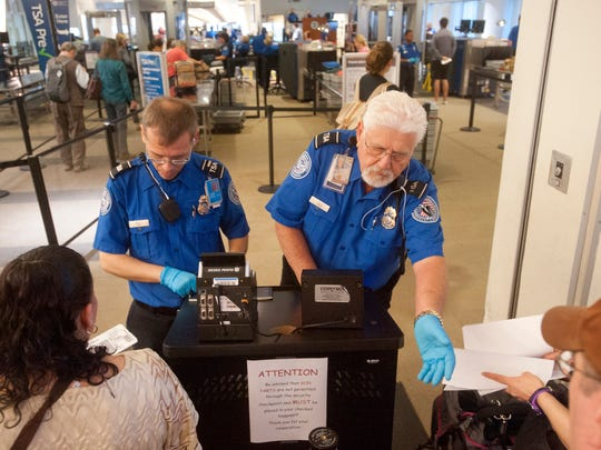 TSA officers screen passengers at the main security checkpoint at Louisville International Airport. The security screening process in Louisville took less than 10 minutes.
