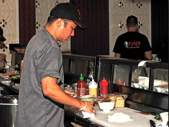 Head sushi chef Long Nguyen prepares food at Tao Asian Cuisine, which recently opened in the Ambassador Town Center.