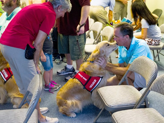 Joan Hedderick, left, and her husband, Dick, say goodbye to Tex at PAWS in Naples during a certificate program on Friday, Aug. 26, 2016. PAWS Assistance Dogs, Inc. provides fully trained and certified service dogs to combat-wounded American veterans and children with disabilities. PAWS dogs spend up to two-and-a-half years in an intensive training program that includes socialization, obedience and detailed task training.